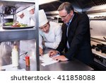 male restaurant manager writing ... | Shutterstock . vector #411858088
