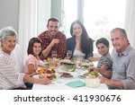 family sitting at dining table... | Shutterstock . vector #411930676