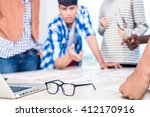 Small photo of Advertising agency team in creative meeting, focus on glasses in foreground