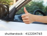 Small photo of close up woman hand showing thumb up through car's window for safety and assurance of driving concept.