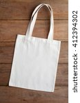 Small photo of White fabric bag on wooden table