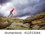 Small photo of Training running and jumping in difficult conditions in a beautiful nature with stormy dramatic sky