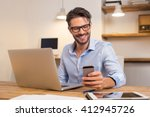 Small photo of Young happy businessman smiling while reading his smartphone. Portrait of smiling business man reading message with smartphone in office. Man working at his desk at office.