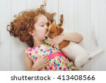 Stock photo little girl and her puppy whispers on wood background 413408566