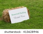 Small photo of A sign and haybale indicating reserved parking for bridal cars.