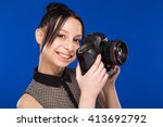 girl holds the camera in hands... | Shutterstock . vector #413692792