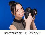 girl holds the camera in hands... | Shutterstock . vector #413692798