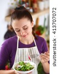 young woman eating fresh salad... | Shutterstock . vector #413707072