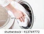 woman hands loading linen into... | Shutterstock . vector #413769772