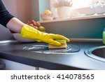 Closeup on woman's hands in yellow protective rubber gloves cleaning kitchen cabinets with sponge.  - stock photo