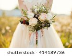Bride Holding Bouquet Of Roses...