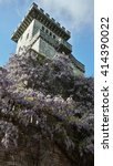 Old tower, overgrown with blooming wisteria, against the sky - stock photo