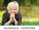 mature  blonde woman in garden. | Shutterstock . vector #414551566