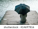 woman with umbrella on a pier | Shutterstock . vector #414697816