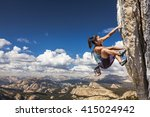 Small photo of Female climber dangles from the edge of a challenging cliff.