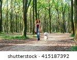 Stock photo girl walking dog in park 415187392