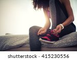 woman tying a shoelace and... | Shutterstock . vector #415230556
