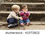 Young Boy Giving Sad Baby Girl...