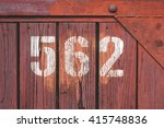 Small photo of White number 5 6 2 on old painted in red and cracked wood planks panel (five hundred sixty-two)