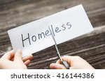 Small photo of holds card with text homeless on old wood plate