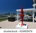 Upscale outdoor terrace with pergola, a bar, and dining room, accented with a red kinetic sculpture designed by the artist Ralfonso. - stock photo