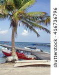 Small photo of AMBERGRIS KEY, BELIZE - CIRCA MAY 2014: Boats pulled up on the beach, under a palm tree, beside a pier