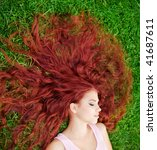 Young pretty girl with red hair lying on grass - stock photo