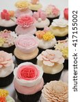 Small photo of Flower fondant cupcakes - pastel pink set in indoor lighting