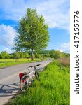 Small photo of A mountain bike parked on road along along rural landscape near Krakow, Poland