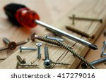 Small photo of Many scattered screws, detail of screw screwed into a wooden plank, screwdriver in the background