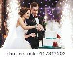 happy bride and groom cut the... | Shutterstock . vector #417312502