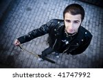 Small photo of Young handsome musician in urban background