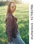 Small photo of Fashionable girl in a leather jacket and sunglasses walking outdoors against the wind