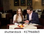 cheerful couple with menu in a... | Shutterstock . vector #417966865