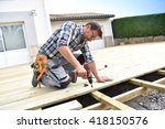carpenter building wooden deck  | Shutterstock . vector #418150576