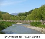 Suspension bridge across the river, green grass and trees on the embankment, the mountains on the horizon                             - stock photo