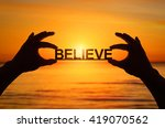Small photo of Silhouette, Close up Hand holding BELIEVE text with blurred sea sunset. sunlight effect.