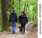 Stock photo middle aged couple walking their two dogs in forest 419182885