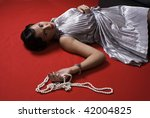 Dead young woman on the floor. Studio shot in a retro style - stock photo