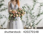 Stock photo wedding bridal bouquet bride in wedding dress standing on a white background holding a bouquet 420270148