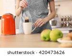 woman making tea in the kitchen | Shutterstock . vector #420473626