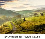 stone steps down the hill in to village in foggy mountains at sunrise - stock photo