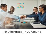 Small photo of Multiracial business team signalling their commitment to each other by reaching across the table in the office to stack hands as they smile at each other