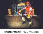 Bulldozer Works Concept. Young Caucasian Men Seating and Relaxing on Bulldozer Blade. Happy Construction Worker. Ground Works. - stock photo