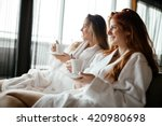 women in bathrobes enjoying tea ... | Shutterstock . vector #420980698