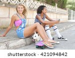 Small photo of Two ethnically diverse teenager girls friend together in a suburban street, carrying a white dog pet, looking and smiling at camera, outdoors. Active adolescent young women with animal on holiday.