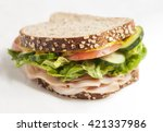 Small photo of turkey sandwich with vegetables, bread with cereals, close up shot with selective focus on white background