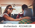 Happy young woman looking back with man driving car. Couple in a car going on roadtrip. - stock photo