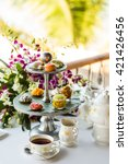 Small photo of Afternoon tea ceremony, beach restaurant with sea view, flowers