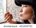 Small photo of woman in cafe lick the spoon, delicious taste